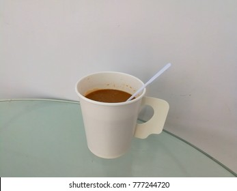 A cup of white coffee is placed on a clear glass table.