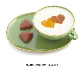 a cup of white coffee with two hearts made of cinnamon and cacao and two heart shaped chocolate cookies