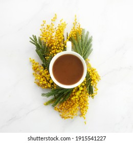 Cup of white coffee with yeallow mimosa flowers. Flat lay, top view.