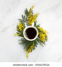 Cup of white coffee with yeallow mimosa flowers. Flat lay, top view