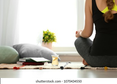 Cup of white tea near woman practicing yoga indoors