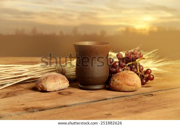 Copa de vino, pan. uvas y trigo en mesa vintage con puesta de sol caliente en segundo plano