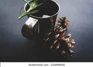 Cup of winter tea with green rosemary and pine cones closeup over dark background. Hugge cozy atmosphere with hot winter tea with christmas decor and aromatic rosemary been branch. Design background.