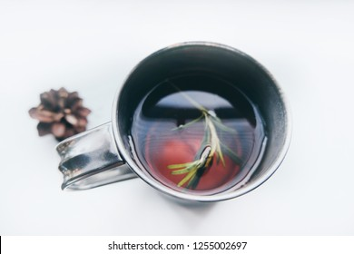 Cup of winter tea with green rosemary and pine cones closeup over white background. Hugge cozy atmosphere with hot winter tea with christmas decor and aromatic rosemary been branch. Design background.