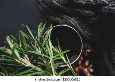 Cup of winter tea with green rosemary and pine cones top view over dark background. Hugge cozy atmosphere with hot winter tea with christmas decor, rosemary, knitted plaid mock up. Design for cards.