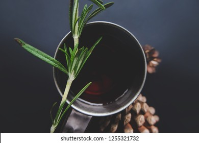 Cup of winter tea with green rosemary and pine cones top view over dark background. Hugge cozy atmosphere with hot winter tea with christmas decor, aromatic rosemary green branch. Design background.