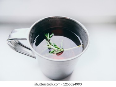 Cup of winter tea with green rosemary closeup over white background. Hugge cozy atmosphere with hot winter tea with christmas decor and aromatic rosemary green branch. Design background.