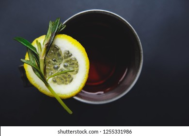 Cup of winter tea with green rosemary closeup over dark background. Hugge cozy atmosphere with hot winter tea with christmas decor, lemon,rosemary green branch. Design background for xmas cards.