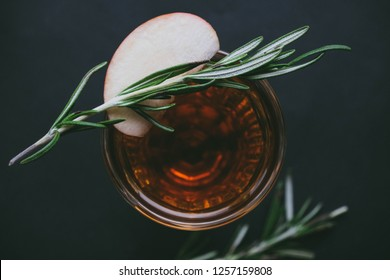 Cup of winter tea with green rosemary closeup over dark background. Hugge cozy atmosphere with hot winter tea with christmas decor, apple,rosemary green branch. Design background for xmas cards.