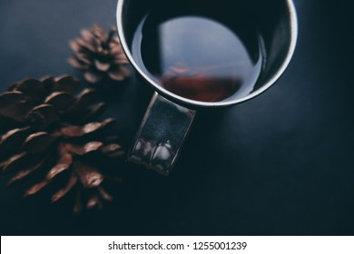 Cup of winter tea with pine cones closeup over dark background. Hugge cozy atmosphere with hot winter tea with christmas decor and aromatic rosemary. Design background for christmas cards lettering.