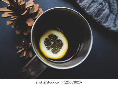 Cup of winter tea with pine cones closeup over dark background. Hugge cozy atmosphere with hot winter tea with christmas decor and lemon. Design background for christmas cards lettering.