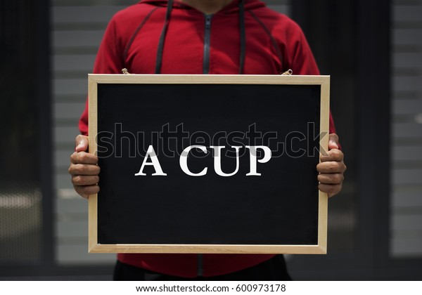 A cup written on blackboard with someone is holding it