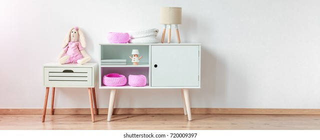 Cupboard with pink decorations standing by a white wall next to a tiny chest of drawers with a stuffed animal rabbit on top of it in a spacious interior