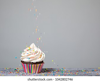 A Cupcake being decorated with colorful Sprinkles.