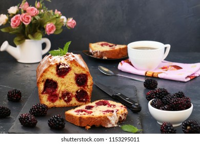 Cupcake with blackberries is located on a dark background. Section of a cake with a slice in the foreground. On the table there is a cup of coffee, flowers and a fresh blackberry.