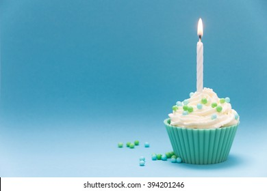 cupcake with burning candle and blue background