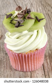 cupcake with butter cream,  kiwi slices and powdered chocolate curls