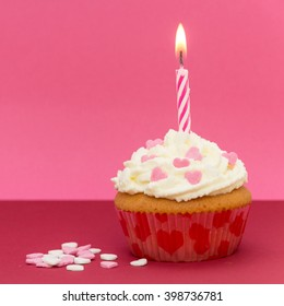 cupcake with candle and pink background