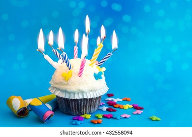 cupcake with candles on blue background with decoration