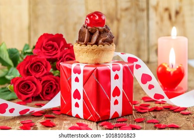 Cupcake with cherry over red gift box in front of bouquet of red roses and candles on wooden background. Valentines day concept. Mothers day concept. Focus on cake.