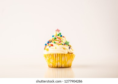 Cupcake with colorful sprinkles isolated on white background, centered