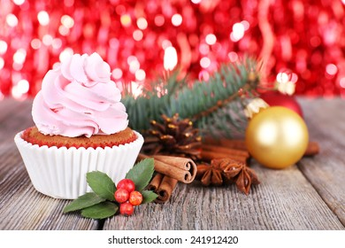 Cup-cake with cream and Christmas decoration on wooden table and shine brightly background