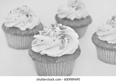 Cupcake with cream and gold confectionery sprinkling, with blurred background. Black and white. Picture for a menu or a confectionery catalog.