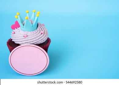 Cupcake with crown and pink heart over blue background with blank board for text, Gift for celebration