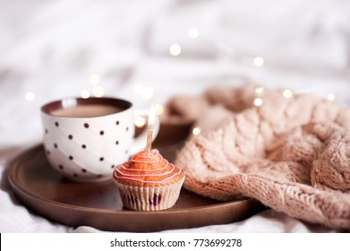 Cupcake with cup of coffee with knitted cloth on wooden tray in bed close up. Good morning.