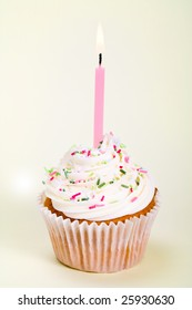 Cupcake decorated with sugar sprinkles and a single candle