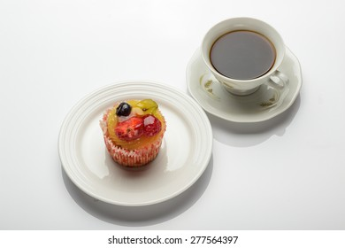 Cupcake with fruits and cup of coffee
