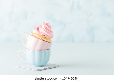 Cupcake with gentle pink cream decoration in two cups on blue pastel background. Horizontal banner for birthday or wedding congratulation card.
