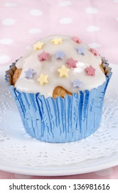 cupcake with icing and colorful stars on a white plate