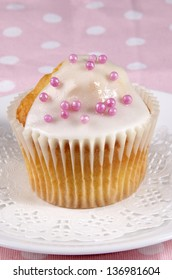 cupcake with icing and pink pearls on a white plate