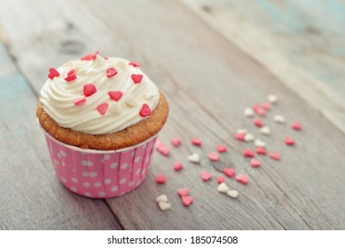 Cupcake with icing in shape of hearts on wooden background