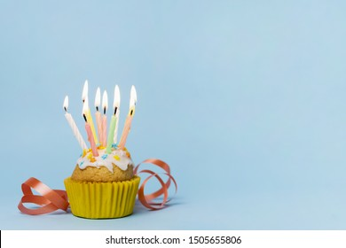 Cupcake with many lit candles and copy space