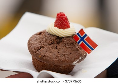 A cupcake  with Norwegian flag vanilla cream and fresh organic raspberry. Celebration of May 17th in Oslo, Norway. Happy holidays with family. National day in Scandinavia.