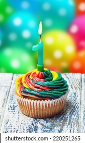 Cupcake with number one on the background of balloons.