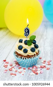 Cupcake with a numeral nine candle on a table