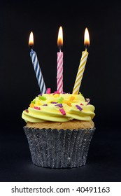 cupcake on black with 3 candles on black