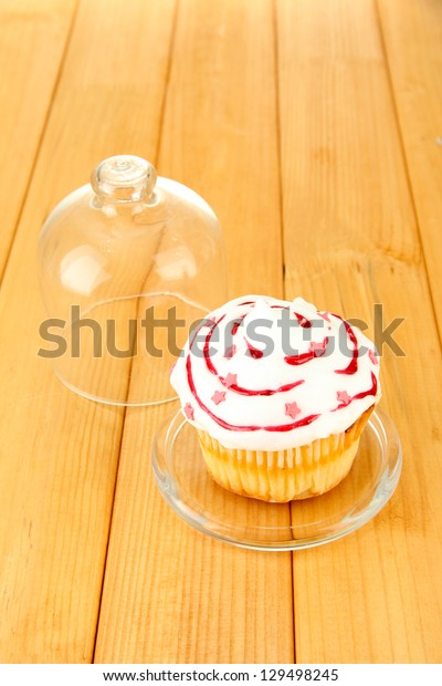 Cupcake on saucer with glass cover, on wooden background