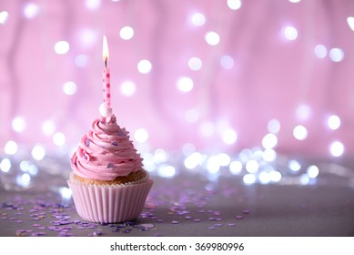 Cupcake with pink cream icing and candle on a glitter background