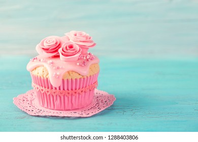 Cupcake with pink flowers on a blue wooden background