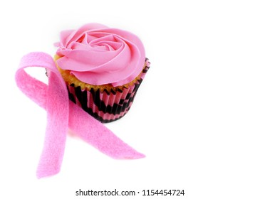 A cupcake with pink icing and a pink felt awareness ribbon on white background for Breast Cancer Awareness month in October. Copy space
