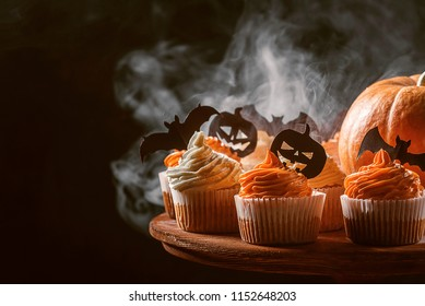 cupcake and pumpkin on a dark background. sweets for the celebration of Halloween.
