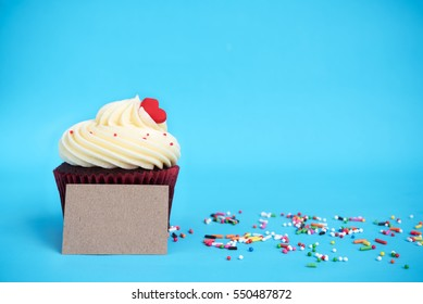 Cupcake with red heart, colorful sprinkles and brown note over blue background with copy space