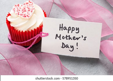 "Cupcake in red wrapper with white frosting and topped with a candy heart by a gift tag that reads ""Happy Mother's Day"" for Mothers' Day, birthdays, and similar occasions."