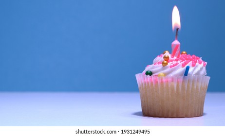 Cupcake with single birthday candle burning and sugar sprinkles icing on blue background. Delicious muffin decoration. Homemade vanilla cup cake with buttercream frosting. Shallow depth of field.