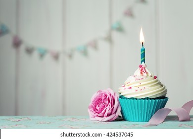Cupcake with single candle and pink rose