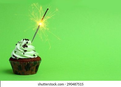cupcake with sparkler against a green background